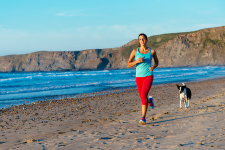 Fitness woman and dog on running workout at the beach  Sporty female runner training on summer sunset  Stock Photo