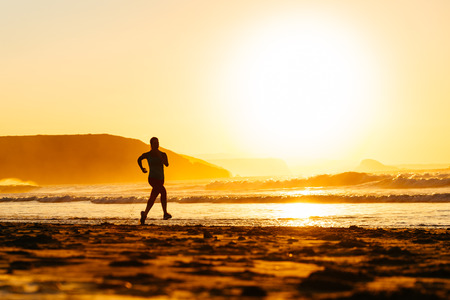 Woman athlete silhouette running on beautiful orange summer sunset or morning at the beach  Fitness runner lifestyle scene  photo