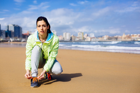 fitness motivation: Fitness woman getting ready for running challenge at city beach in Gijon, Asturias, Spain. Female runner lacing sport shoes before training.