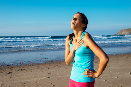 consequence: Exhausted female runner suffering painful angina pectoris or asthma breathing problems after training hard on summer  Running overtraining consequence