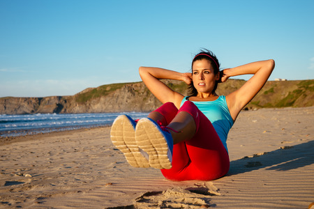 sit ups: Fitness woman doing sit ups exercising on beach  Sporty girl workout outdoors on summer