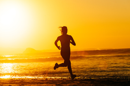 Female runner training hard on beautiful summer sunset or morning  Woman running fast at the beach  photo