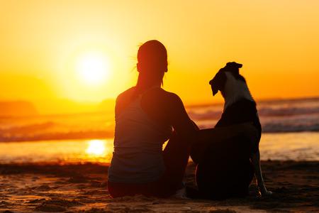 dog: 모래 해변에 앉아 바다 여름 일출 또는 일몰을 즐기는 편안한 여자와 개 스톡 사진