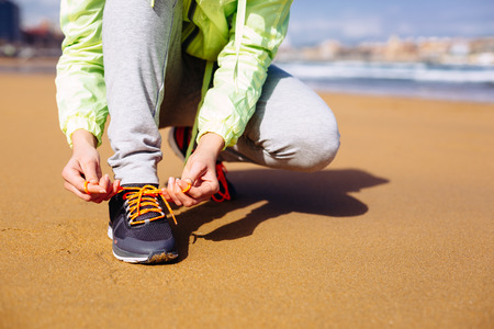 Fitness woman getting ready for running challenge at city beach in Gijon, Asturias, Spain  Female runner lacing sport shoes before training