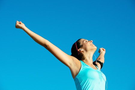 Successful happy fitness woman raising arms to the sky after sport achievement outdoor  Sporty girl enjoying freedom