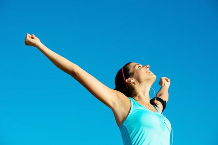 Succesvolle gelukkige fitness vrouw het verhogen van armen naar de hemel na de sport prestatie outdoor Sportief meisje genieten van vrijheid