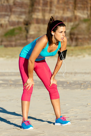 Exhausted fitness woman taking a break after running on summer at the beach   Tired female runner resting Stock Photo - 27334030