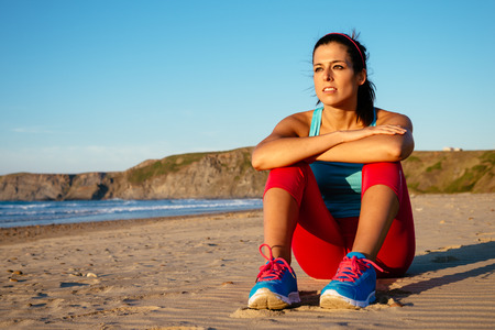 rest in peace: Relaxed fitness woman resting after exercising and watching the sun on summer sunset at beach