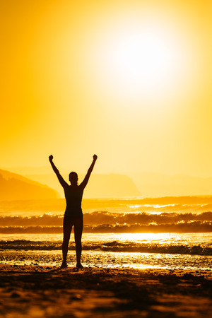 Fitness woman celebrating sport success on beautiful summer sunset or sunrise on the beach Successful female runner silhouette raising arms to the sun