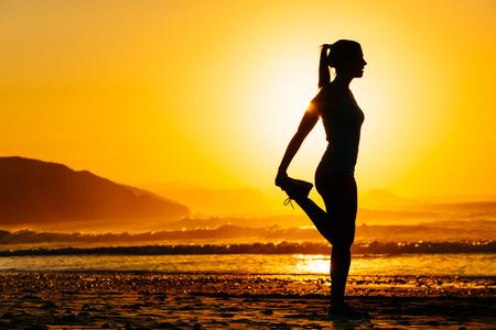 Fitness Frau, die Ausübung und Stretching Beine auf schönen Sommer Sonnenuntergang am Strand oder am Morgen Läuferin Erwärmung oder Abkühlung