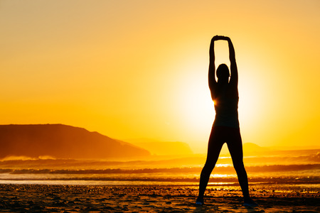 body silhouette: Fitness woman exercising and stretching arms on beautiful summer sunset or morning at beach  Female doing relaxing yoga and breathing exercises