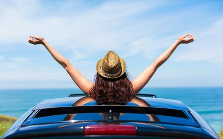夏休み旅行車サンルーフを海に向かって傾いて海岸にリラックスした女性の後姿
