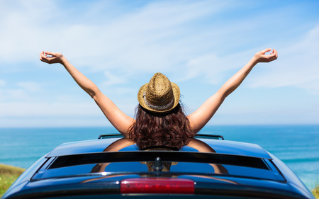 arms raised: Rear view of relaxed woman on summer travel vacation to the coast  leaning out car sunroof towards the sea