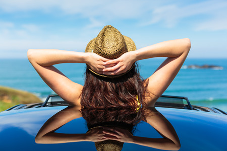 Rückansicht der Frau entspannt auf Reisen Sommer Urlaub an der Küste lehnte sich aus dem Auto-Schiebedach in Richtung Meer Standard-Bild