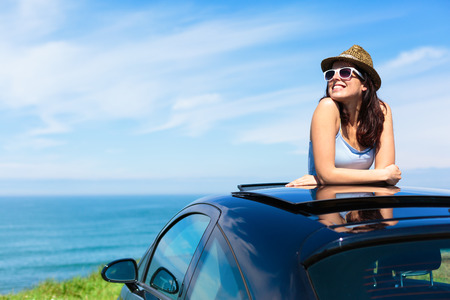 Relaxed happy woman on summer travel vacation to the coast leaning out car sunroof with the sea on background