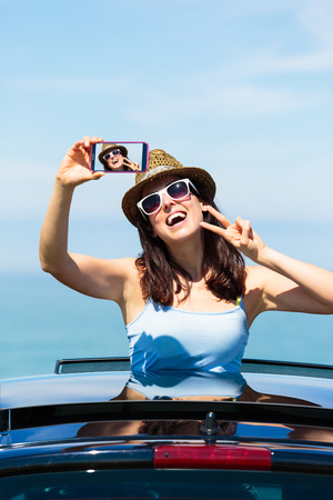 Happy woman taking smartphone selfie photo on car summer travel vacation to the coast  Brunette girl  leaning out car sunroof with the sea on background