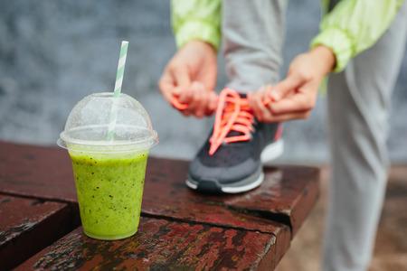 녹색 해독 스무디 컵 비오는 날 운동 및 건강한 라이프 스타일 개념에 운동하기 전에 운동화 끈으로 묶는 여자