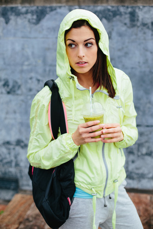 Urban fitness woman drinking vegetable detox smoothie after\ workout.