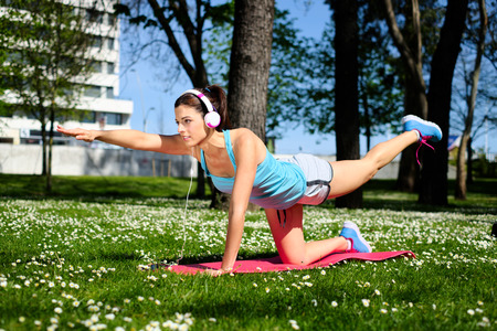 Fitness spring or summer workout outdoor. Fit woman working out and doing stretching exercises in city park. photo