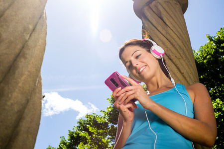 rest in peace: Relaxed fitness woman taking a rest for listening music and texting  message with smartphone after workout  Sport and healthy lifestyle concept  Stock Photo