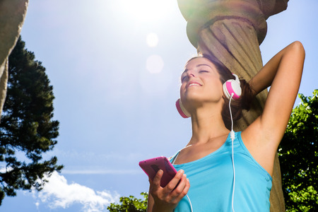 rest in peace: Relaxed fitness woman taking a rest and listening music with smartphone and headphones after workout  Sporty happy girl relaxing  Sport and healthy lifestyle concept  Stock Photo