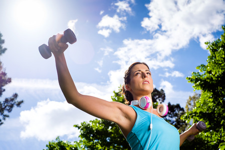 Fitness woman working out with dumbbells in city park  Spring or summer exercising workout with weights  Urban sport lifestyle concept  photo