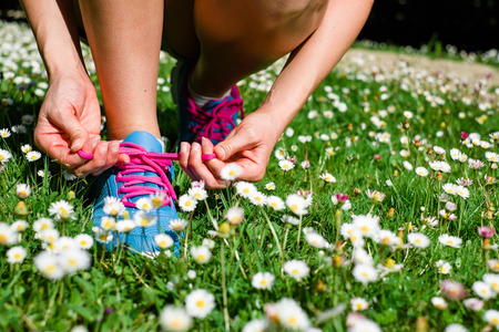 tying: Female athlete getting ready for running in spring park  Fitness workout outdoor concept  Stock Photo