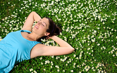 Female athlete resting and relaxing after workout  Woman lying down on grass and spring flowers  Healthy lifestyle and happiness concept