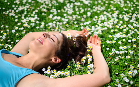 ojos cerrados: Atleta de sexo femenino que descansa y relaja después de entrenamiento Relajado mujer alegre que se acuesta en la hierba y las flores del resorte del estilo de vida saludable y el concepto de la felicidad