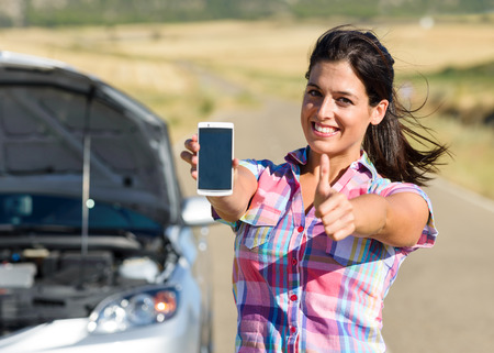 Cheerful woman calling to car insurance service after accident or engine breakdown during roadtrip  Positive female showing smartphone screen  photo