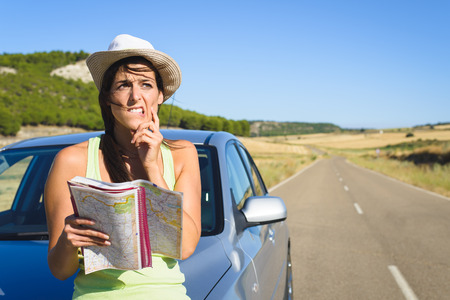 Confused lost woman on car roadtrip travel problem searching in road map
