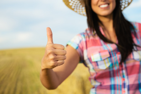 achiever: Agriculture business success concept  Female farmer with thumbs up for approving gesture on country rural field background