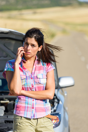 Upset desperate woman calling to car insurance service after accident or engine breakdown. Roadtrip vacation problem concept. photo