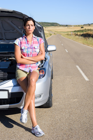 Upset sad woman waiting for road service help after car accident or engine breakdown. Roadtrip vacation problem concept. Stock Photo
