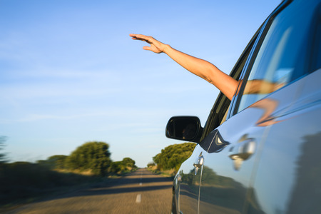 roadtrip: Woman sticking arm out of the car window on roadtrip. Female driver hand feeling the air and freedom.