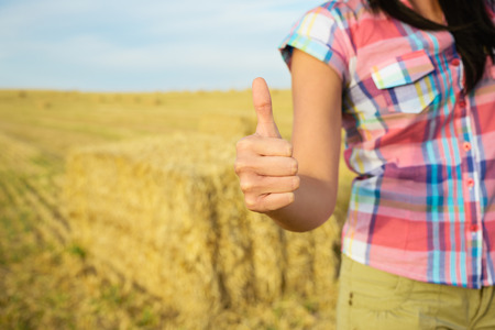 achiever: Agriculture business success concept. Female farmer with thumbs up for approving gesture on country rural field background.