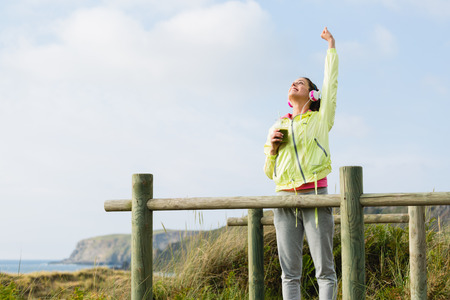 achiever: Successful fitness woman drinking detox smoothie after exercising at beach on spring or summer. Joyful fit brunette girl celebrating sport success.