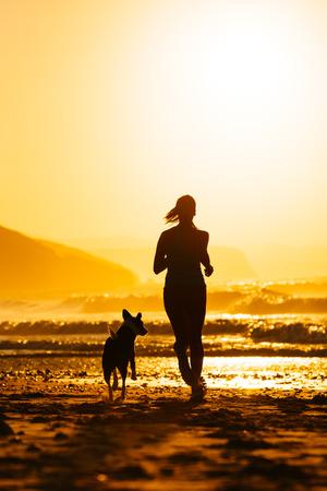 siluetas de animales: Mujer y perro que se ejecutan en la hermosa puesta de sol de verano o la salida del sol en la playa de la mujer atleta con su entrenamiento de la mascota juntos