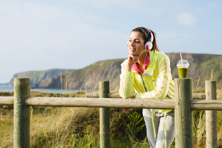 Pensive and relaxed fitness woman resting after exercising at beach on spring or summer Fit brunette girl with detox smoothie drink