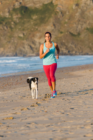 Fitness woman with dog running and exercising at beach on summer  Brunette female athlete training with her pet  photo