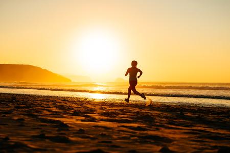 夏のトレーニング ランナーのビーチで美しい夕日や朝で実行されている女性の運動選手 写真素材