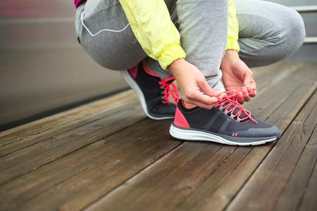 都市の実行前に女性ランナー抱き合わせスポーツ靴レース挑戦スポーティな認識できない女性フィットネスと健康的なライフ スタイルのコンセプト