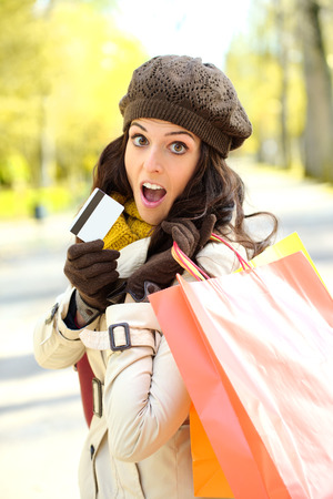 Fashion trendy woman showing credit card and carrying shopping bags after buying in autumn  Amazed shopper jaw dropping  photo