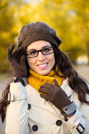 warm clothes: Moda donna allegra indossando occhiali e vestiti caldi in autunno Bella bruna con occhiali, impermeabile, berretto di lana e sciarpa Archivio Fotografico