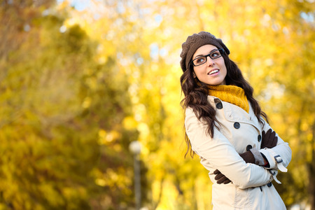 Cheerful fashion woman wearing glasses and warm clothes in autumn  Beautiful brunette with eyewear, raincoat, wool cap and scarf