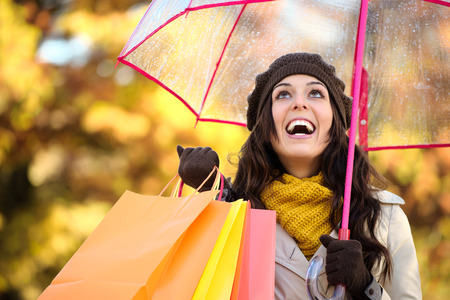 Happy woman holding shopping bags and umbrella under autumn rain. Brunette fashion female shopper outside in fall season.