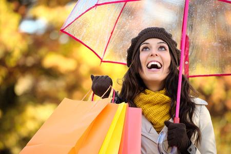 lluvia: Mujer feliz con sus bolsas de compra y paraguas bajo la lluvia de otoño. Comprador femenino moda Morena fuera de la temporada de otoño.