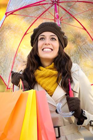 Happy woman holding shopping bags and umbrella under autumn rain. Brunette fashion female shopper outside in fall season. photo