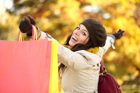 Blissful woman holding shopping bags and having fun buying in autumn rain. Successful female shopper outside in fall season. photo
