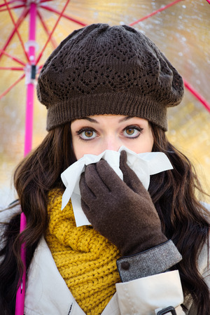 cold weather: Woman with cold or flu blowing her nose with a tissue and sneezing under autumn rain. Brunette female wearing warm clothes, scarf, cap and gloves.